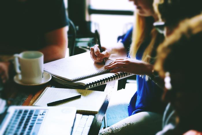 ομάδα ανθρώπων με υπολογιστές και σημειωματάρια