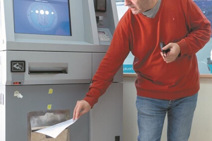 άντρας σε ATM παραλαμβάνει πιστοποιητικό