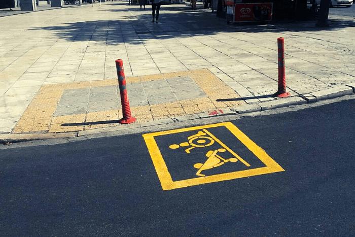 ειδική σήμανση στην άσφαλτο αναπηρικό σήμα και καρότσι μωρού (κίτρινα εικονίδια)