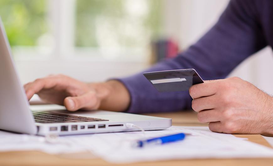 άντρας που πληρώνει μέσω κάρτας από το λαπτοπ του